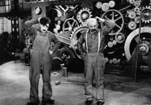 Image les temps modernes 2 hommes en réflexion devant une machine à angrenage